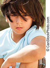 Close-up portrait of a young boy looking off in the distance