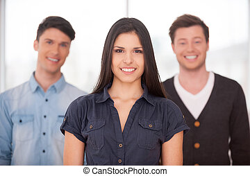 Real leader. Attractive young woman smiling while two men standing behind her