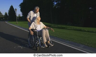 Real love of senior couple with paralyzed wife in park