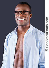 Real macho. Handsome young black man in unbuttoned shirt smiling at camera while standing against grey background
