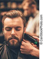 Real man grooming. Close-up of handsome man getting beard haircut by hairdresser at barbershop