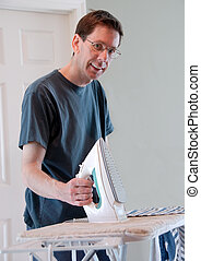 Real Men Iron Clothes - A happy, smiling man doing his own...