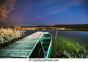 Real Night Sky Stars Above Old Pier With Moored Wooden Fishing Boat. Natural Starry Sky And Countryside Landscape With Lake River In Early Spring Night. Russian Nature