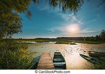 Real Night Sky Stars And Moonrise Above Old Pier With Moored Wooden Fishing Boat. Natural Starry Sky And Countryside Landscape With Lake River In Early Spring Night. Russian Nature
