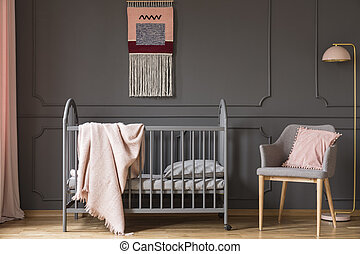 Real photo of a baby crib with a blanket standing next to an armchair with a cushion and a lamp in child's room interior