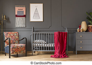 Real photo of a baby crib with a red blanket standing between an arnchair and lamp, and a cupboard with ornaments in child's room interior