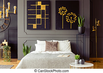 Real photo of a bedroom interior with big, black paintings with golden accents, double bed and plants