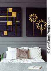 Real photo of a bedroom interior with black and gold paintings, double bed with pillows and book