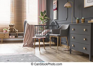 Real photo of a cot standing next to an armchair, lamp and cupboard in dark and classic baby room interior
