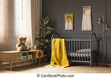 Real photo of a cot with a yellow blanket standing between a low cupboard with a bear and a lamp in baby room interior