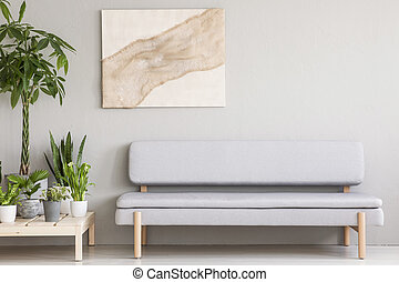 Real photo of a cozy gray couch standing next to a wooden platform with plants in a simple, scandi living room interior