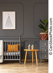 Real photo of a crib with an orange pillow standing next to a yellow stool and a cupboard with a plant in baby room interior with a poster on a wall