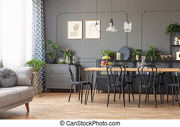 Real photo of a dark flat interior with gray couch, wooden dining table, black chairs and golden posters on the wall in open space living room