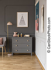 Real photo of a grey cupboard with ornaments standing next to a lamp, armchair and wall with a poster in spacious baby room interior