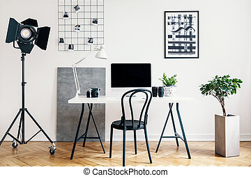 Real photo of a home office interior with a professional lamp, desk, chair, computer and plant. Place your logo on the computer screen
