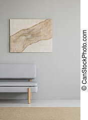 Real photo of a minimal living room interior with a burlap artwork above a gray couch. Place for your lamp