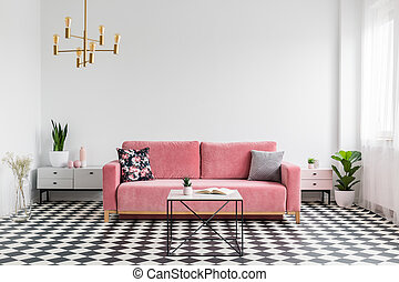 Real photo of a modern living room interior with a checkered floor, pink couch, coffee table and empty, white wall. Place your graphic