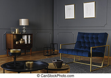 Real photo of a navy blue armchair with a golden frame standing against dark wall with molding in living room interior with gray rug on wooden floor