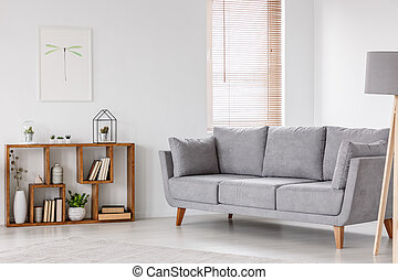 Real photo of a scandi living room interior with gray settee standing near the window, next to a wooden bookcase with plants and books