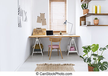 Real photo of a simple home office interior in a bright room with a desk, window blinds and plant