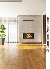 Real photo of a simple, natural living room interior with a tall plant near the window, wooden floor and fireplace in a white, brick wall. Place for your furniture