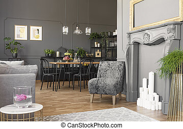Real photo of a spacious and elegant living room interior with golden frame above a faux fireplace standing next to an armchair with vintage pattern