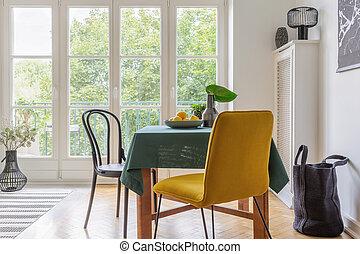 Real photo of a vintage dining room interior with a table, yellow chair and big balcony window