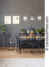 Real photo of an elegant dining room interior with molding on dark wall, black chairs at a wooden table and glass lamps