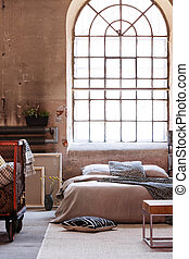 Real photo of an industrial bedroom interior with a big window and double bed