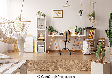 Real photo of bright room interior with hammock, fresh plants and home office corner with wooden desk, chair and decor