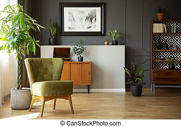 Real photo of dark living room interior with green armchair,...