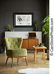 Real photo of green chair standing in grey living room...