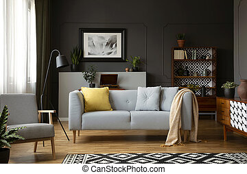 Real photo of grey sofa with pillows standing in dark living...