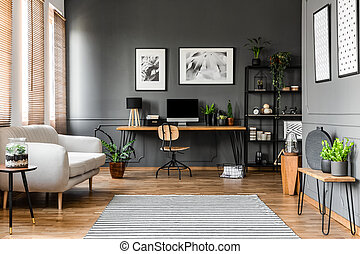 Real photo of open space apartment interior with beige sofa next to the window and desktop computer o a wooden desk