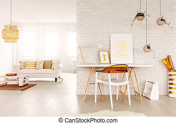 Real photo of open space study corner with desk with two posters and lamp, fresh plants and plastic chair in bright living room interior with windows, couch and DIY coffee table