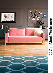 Real photo of powder pink sofa with fur cushion standing in...