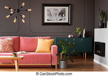 Real photo of powder pink sofa with open book standing in...