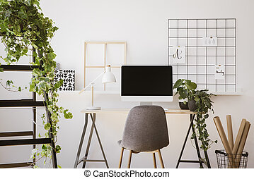 Real photo of white apartment interior with fresh plants, paper rolls in basket, organizer on wall and wooden desk with empty screen monitor and lamp