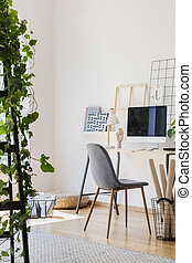 Real photo of white living room interior with study corner desk with empty screen monitor, metal lamp and decor