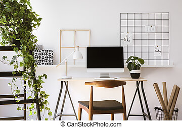 Real photo of wooden desk with metal lamp, fresh plant and empty screen monitor standing in white flat interior