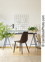 Real photo of workspace desk with notebooks, metal lamp and fresh plant in white room interior with carpet, leather chair and metal organizer on wall