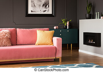 Real photo of yellow pillow placed on powder pink settee...