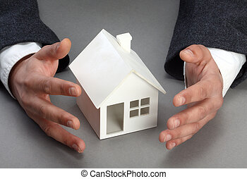 Real property concept - Hands and house model. Real property...