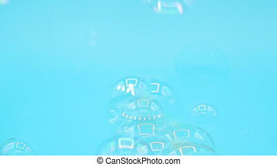 Real soap bubbles flying on blue pastel background.