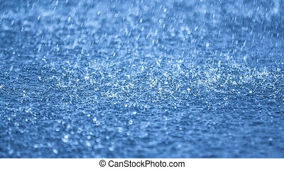 Real time raindrops falling on blue water, DOF
