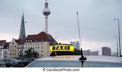 Real time shot of Berlin TV tower with taxi sign foreground