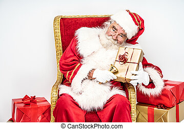 Real white bearded Santa Claus holding gold bell and Christmas gifts.