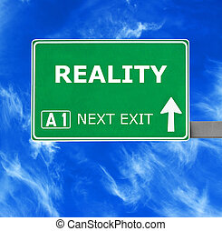 REALITY road sign against clear blue sky