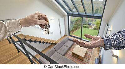 Realtor giving house key to buyer in Modern living room with...