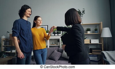 Realtor giving key to girl and guy shaking hands, happy...